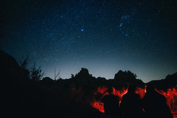 Three friends silhouetted against the night sky