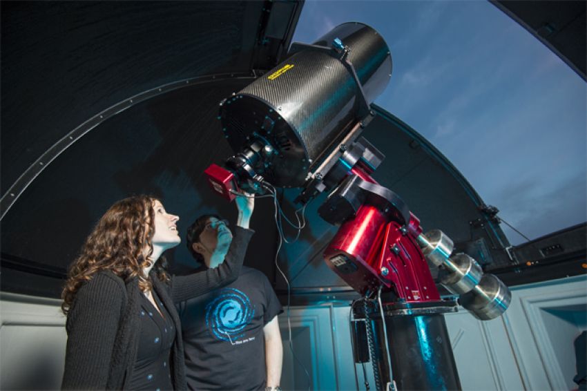 Dr. Collins is in the observatory looking through a telescope