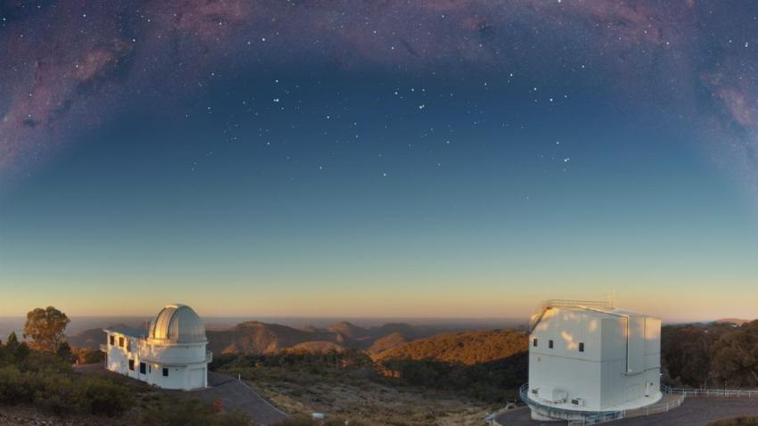 Photograph of two telescope domes, with the Milky Way observed overhead