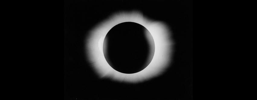 The Sun is a big black circle with bursts of light protruding around its edge as it is eclipsed by the Moon.
