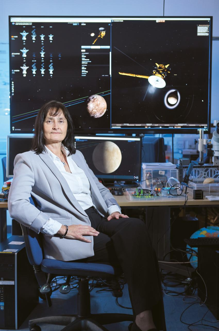 Prof Dougherty sitting in front of monitors showing space objects.