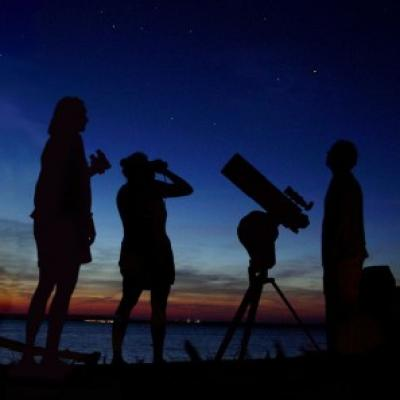 Three people enjoy the summer sky over the Delaware river, NJ, USA during the Perseid meteor shower in August, 2006.